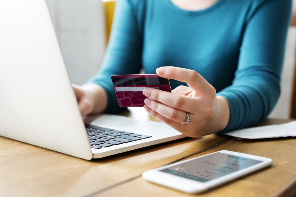 woman holding credit card with computer