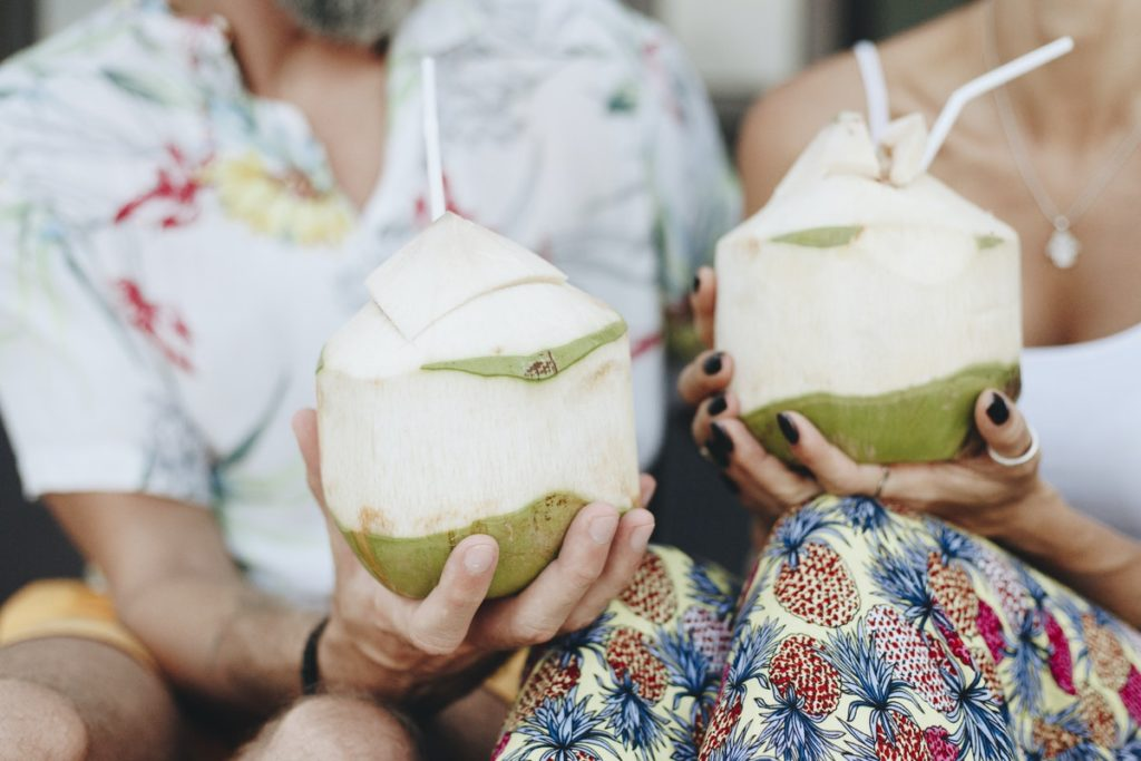 Couple sitting on beach holding coconut drinks in their hands