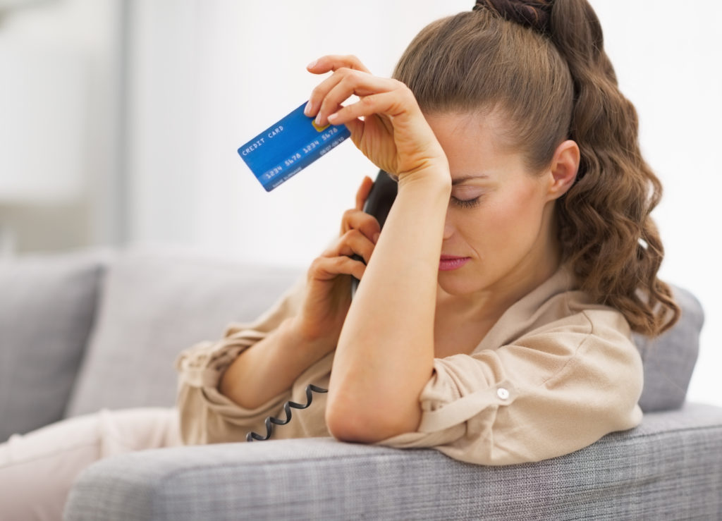 Frustrated young woman with credit card and talking phone