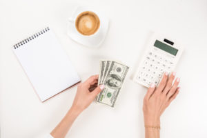 hands holding money and calculator budgeting