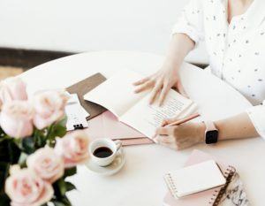 woman writing in notebook with pink roses