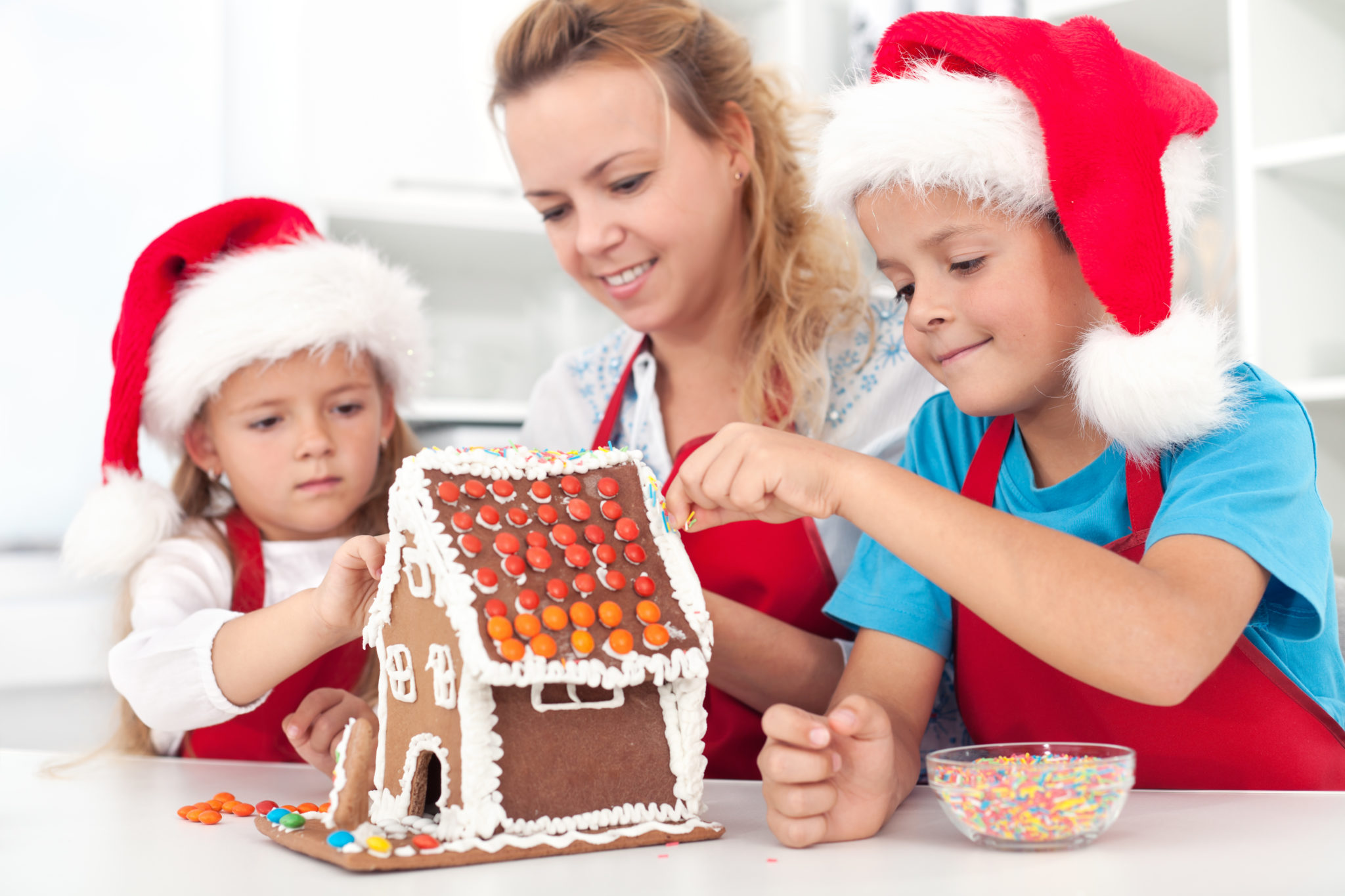 family decorating gingerbread house